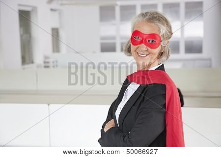 Portrait of smiling senior businesswoman in superhero costume in office