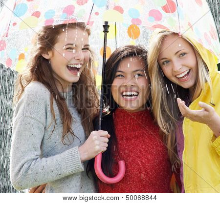 Three Teenage Girl Sheltering From Rain Beneath Umbrella
