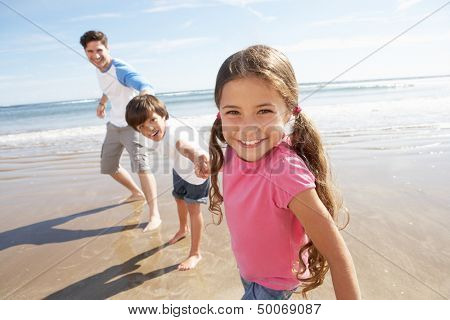 Father And Children Having Fun On Beach Holiday