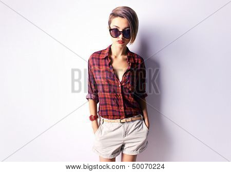 Portrait of a stylish woman with a tempting look from behind sunglasses