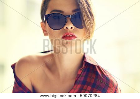 Close-up portrait of a sensual woman in sunglasses with one naked shoulder
