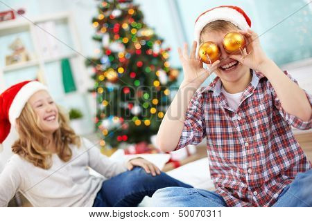 Portrait of happy lad holding decorative toy balls by his eyes and laughing on Christmas evening