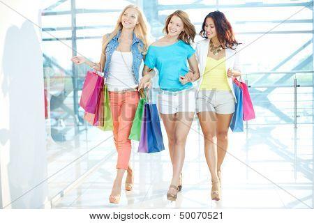 Lindas namoradas com paperbags andando do centro de comércio