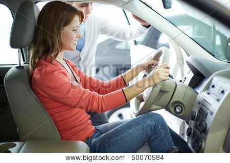 Smiling young woman being glad about her newly-bought car