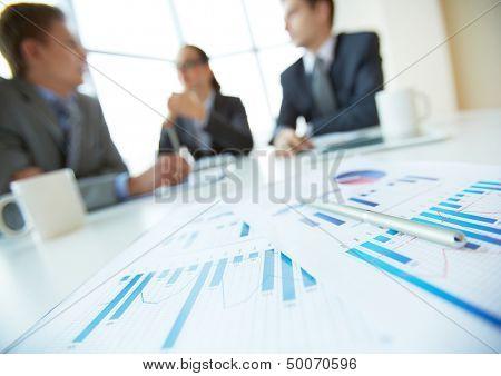 Primer plano de mentir sobre el escritorio, oficinistas en el fondo de documentos de negocios
