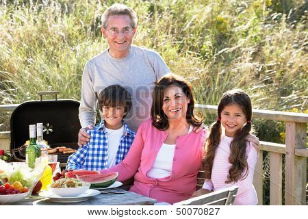Grandparents And Grandchildren Having Outdoor Barbeque