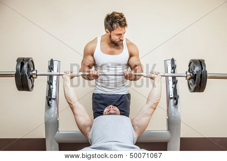 A handsome young muscular sports man doing weight lifting and gets help from his friend