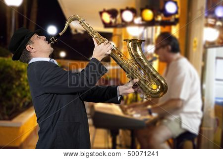 Saxophonist. Men playing on saxophone against the background of rock cafe