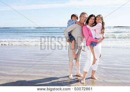 Grandparents And Grandchildren Having Fun On Beach Holiday