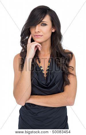 Pensive elegant dark haired model posing with finger on her cheek on white background