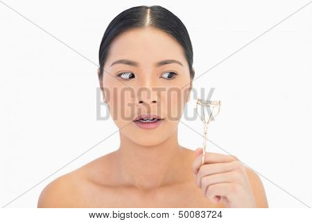Apprehensive natural model holding eyelash curler on white background