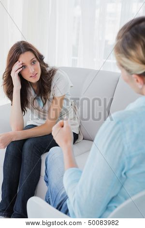 Upset woman sitting with her therapist talking to her and advising her