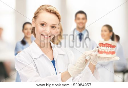 healthcare, medical and stomatology concept - attractive female doctor with toothbrush and big jaws