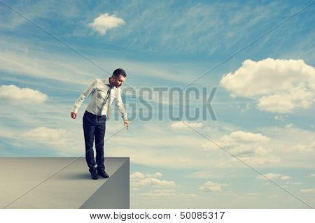 frightened businessman standing over the precipice and looking down