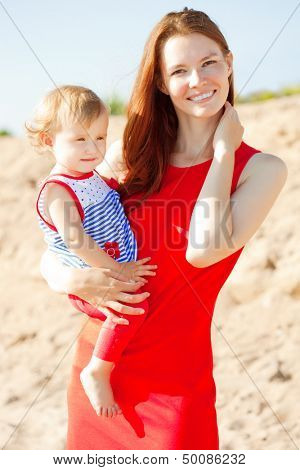 Beauty Mom and baby outdoors. Happy family playing on the beach. Mom and baby. Mother  and child.