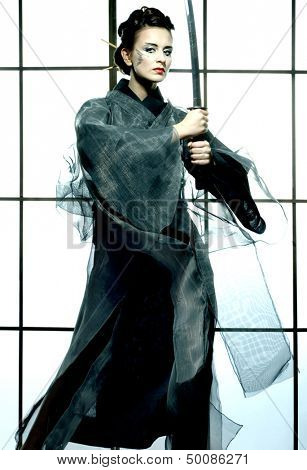 beautiful japanese grey kimono woman with samurai sword in traditional room