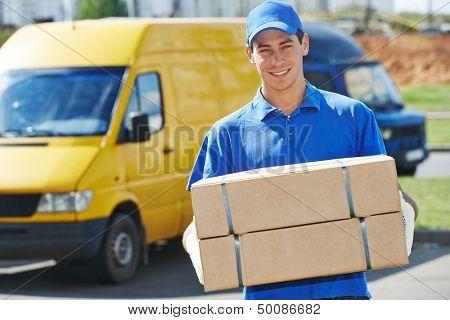 Sonriente joven macho postal mensajero repartidor frente van de carga paquete
