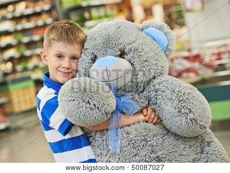 Little child boy with big plush bear gift in toy shop or supermarket store