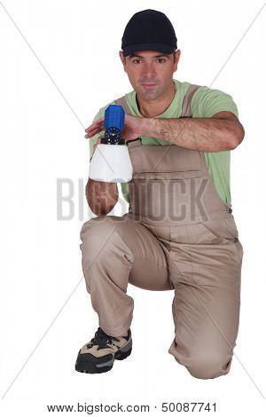 Man kneeling with paint sprayer