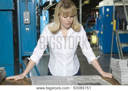 Young serious woman checking newspaper in the factory