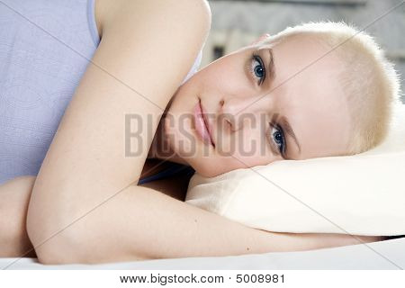 Portrait  Thoughtful Blond Bald Woman Lying On The Bed