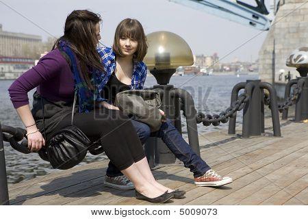 Two Teens Girl Sitting On Embankment.