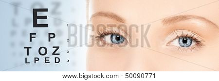 medicine and vision concept - woman's eyes and eye chart