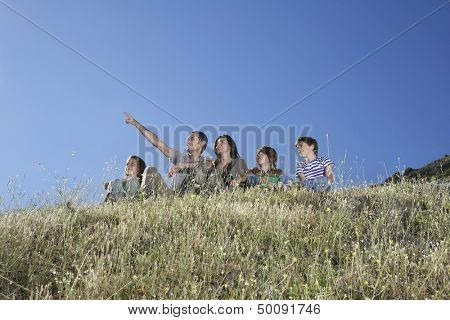 Low angle view of a couple with three children sitting on hill against clear blue sky