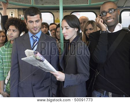 Group of multiethnic commuters in a train with woman reading newspaper