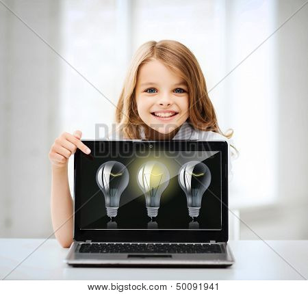 education, school, technology and internet concept - little student girl pointing at laptop pc with light bulbs at school
