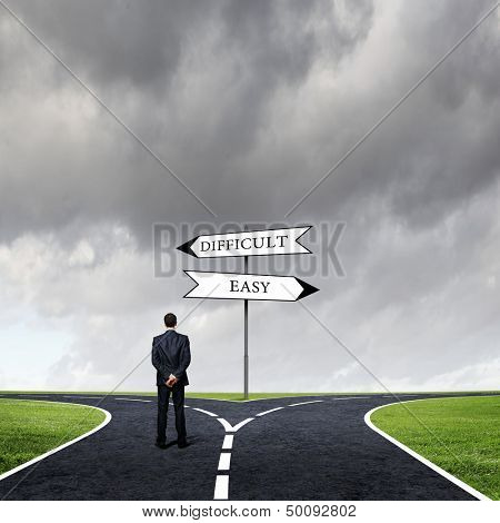 Back view of businessman standing at crossroads. Choice concept