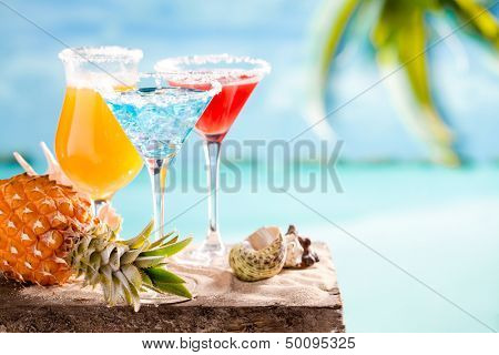 Glasses of cocktails on table near seea on beach