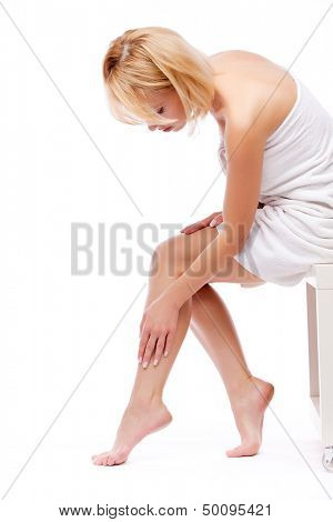 young woman in towel sitting and stroking legs isolated on white background