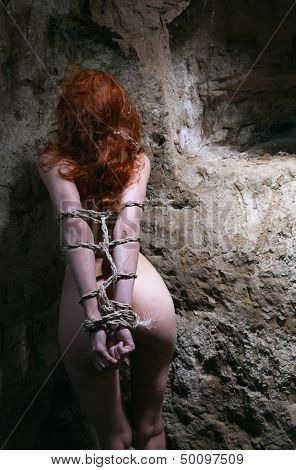 redheaded nude woman bondage in catacomb