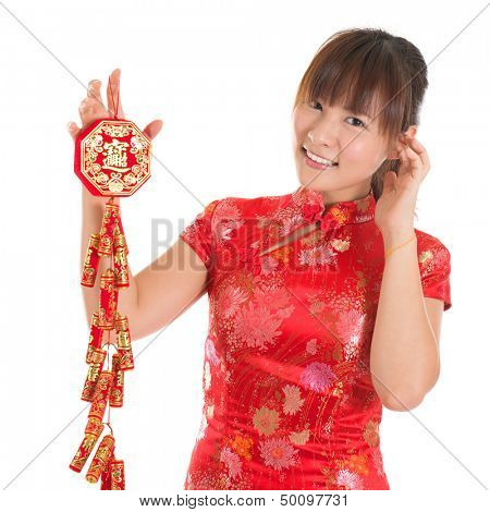 Pretty Asian woman with Chinese traditional dress cheongsam or qipao holding fire crackers. Chinese new year concept, the Chinese words means prosperity.