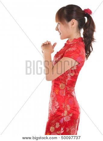Side view Asian woman with Chinese traditional dress cheongsam or qipao respecting on Chinese New Year Festival. Female model isolated on white background.
