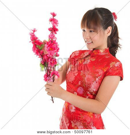 Asian woman with Chinese traditional dress cheongsam or qipao holding plum blossom flower for decorations. Chinese new year concept, female model isolated on white background.