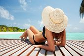 stock photo of sunbathing woman  - Young fashion woman relaxing on the beach - JPG