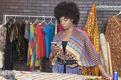 foto of palm-reading  - Attractive African American female fashion designer using cell phone - JPG