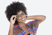 picture of traditional attire  - Portrait of young woman in African print attire wearing glasses over gray background - JPG