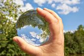 foto of clairvoyance  - In a held glass ball can you seen the landscape behind her - JPG