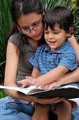 stock photo of babysitter  - Young Hispanic mother reading with toddler son - JPG