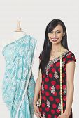 stock photo of dupatta  - Portrait of happy Indian female fashion designer standing by dummy draped in a sari - JPG