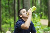 Boy drinking water near jogging trail in the woods