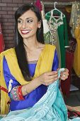foto of dupatta  - Indian female dressmaker looking away while holding sari - JPG