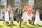 stock photo of fifties  - Guests Throwing Confetti Over Bride And Groom - JPG