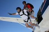 picture of sky diving  - Two skydivers exits a plane on each others backs - JPG