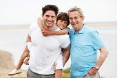 stock photo of 70-year-old  - Male Members Of Multi Generation Family Standing By Sea - JPG