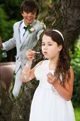 Page Boy And Bridesmaid Blowing Bubbles