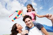 stock photo of kites  - Father And Daughter Having Fun Flying Kite On Beach Holiday - JPG